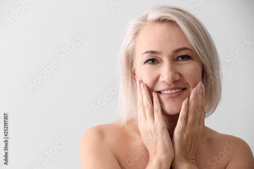 Fototapeta Mature woman giving herself face massage on light background obraz