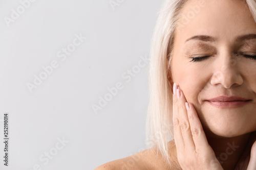 Fotografiet  Mature woman giving herself face massage on light background