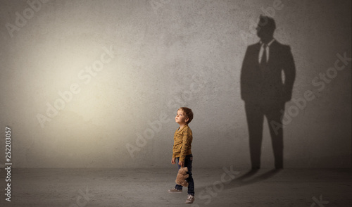 Fototapeta Little boy imagine that he will be businessman and illustrating his future in a big shadow