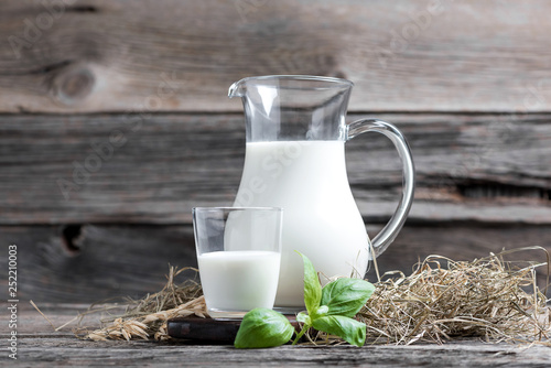 Canvas Print Fresh milk in glasses in front of a rustic vintage background