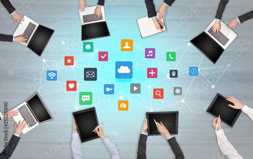 Group of people with devices in hands working in team on tablets, laptops with application concept