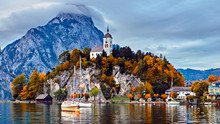 Panoramic Scenic Sunset Over Austrian Alps Lake. Boats, Yachts In The Sunlight Infront Of Church On The Rock With Clouds Over Traunstein Mountain At The Alps Lake Near Hallstatt Salzkammergut Austria