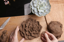 Closeup Of Hands Sculpt Clay Plant Decoration. Hands Modeling Crafts Pottery. Sculpting Clay In The Process.