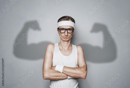 Photo Funny sport nerd with shadow muscle arms over gray wall with copy space