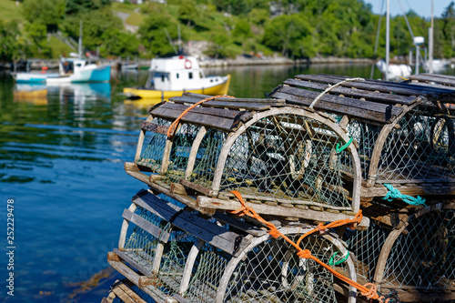 Fototapeta Stacks of traditional wooden lobster traps on the wharf in a Nova Scotia fishing village