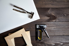 Stretching White Canvas On Wooden Stretcher Bar, Staple Gun And Canvas Pliers On A Brown Table