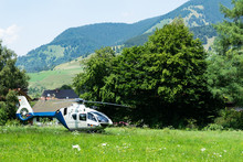 A Police Helicopter Landed In A Mountainous Village In The Field.