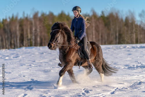 Photo Young Swedish woman riding her Icelandic horse in deep snow