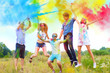 canvas print picture - Cheerful and happy friends soiled by bright paints jumping and laugh in colorful smoke on nature. Company of young people having fun with holi paints on spring summer festival. Holi party concept.