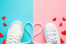 Heart Created From White Shoelaces Between Male And Female Sport Shoes. Bright, Red Hearts. Love Concept. Empty Place For Lovely, Cute Text, Quote Or Sayings On Pastel Blue And Pink Paper. Closeup.