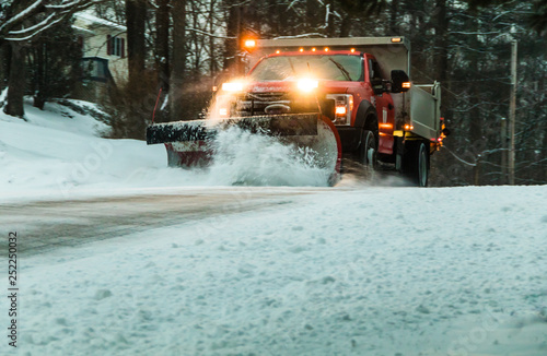 Photo Snow plow at dusk during maintaining road in a winter storm in a residential nei