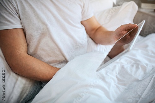 Guy sit in bed in the morning. He hold hand under blanket and masturbating. Man has white tablet in hand. - 252253034