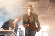 Businessman In Mask Holding Extinguisher Near Coworkers In Office With Smoke