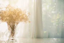 Dried Flowers In A Vase On A W...