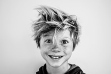 Portrait Of A Young Boy With Freckles And Wild Hair