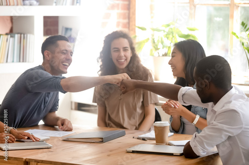 Happy diverse male colleagues students fist bumping at group meeting