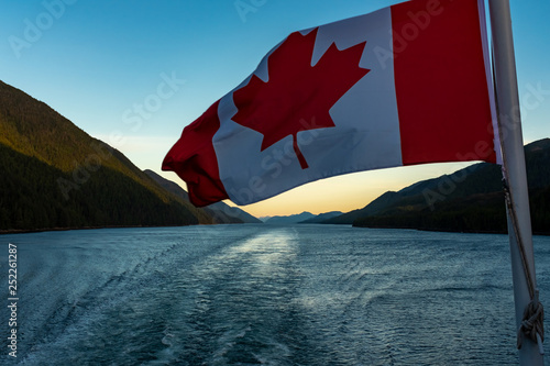 A close up of the Canadian flag flying in the wind at the back of ferry as the boat makes it way through the Inside Passage