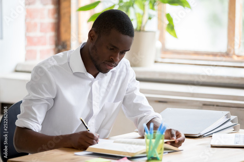 Obraz Serious african man university student studying reading textbook making notes - fototapety do salonu
