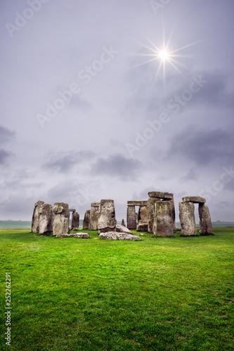Stampa su Tela Sun peaking through the stormy clouds, Stonehenge, England