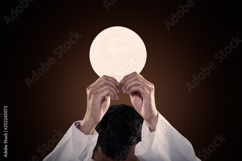 Fotografie, Obraz Pastor hands raising a communion bread