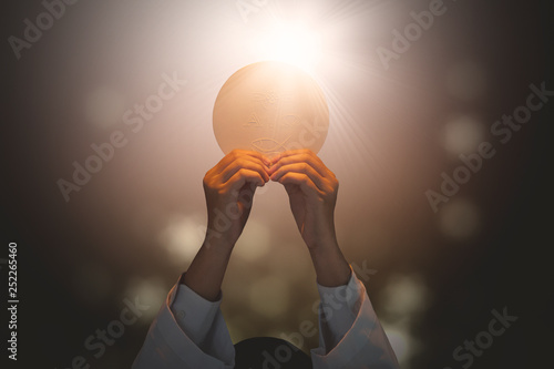 Fototapeta Pastor lifting a bright communion bread