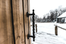 Selective Focus Of Opened Wooden Door With Ironshod Handle And Snowy Landscape On Background