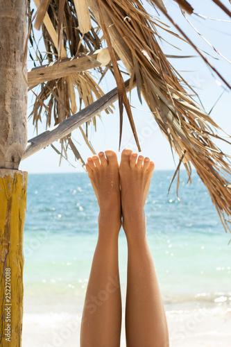 Kobiece stopy na tle pięknego błękitnego morza