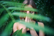 Portrait Of Cute Young Woman Meditating And Doing Namaste Hand In Jungle. Sunny Day