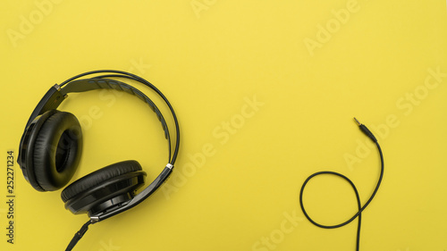 Black headphones and a mini-jack cable on yellow background - 252271234