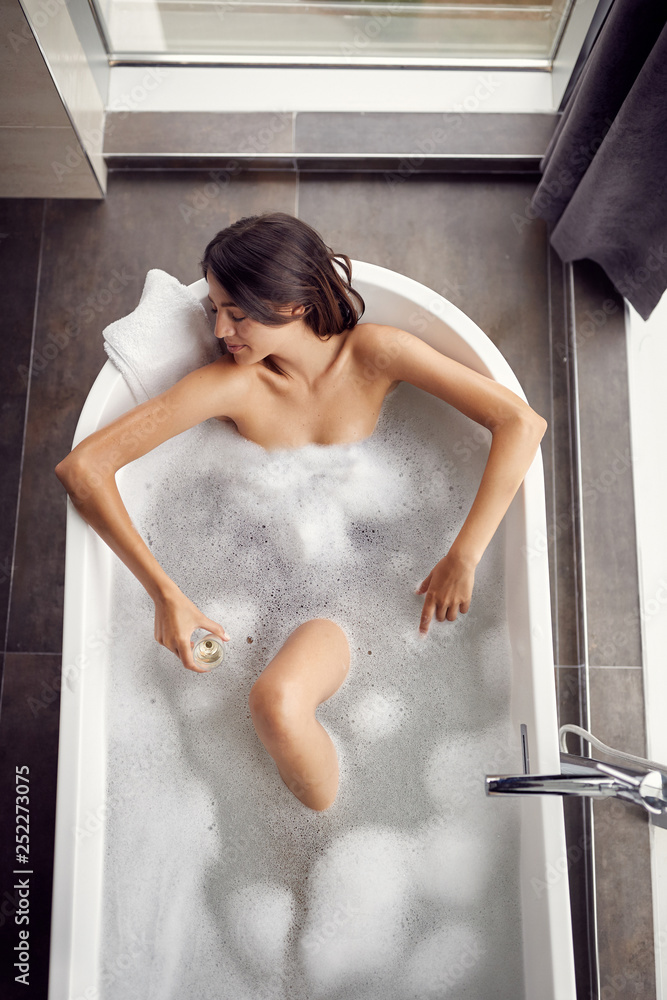 Fototapeta Beautiful woman in the bathroom relaxing in bath with foam top view.