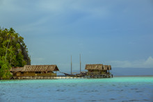 Indonesia. Raja Ampat Archipelago. Cloudy Evening. Coast Of The Island With A Pier For Boats And Houses On Stilts. Two-masted Schooner In The Background.