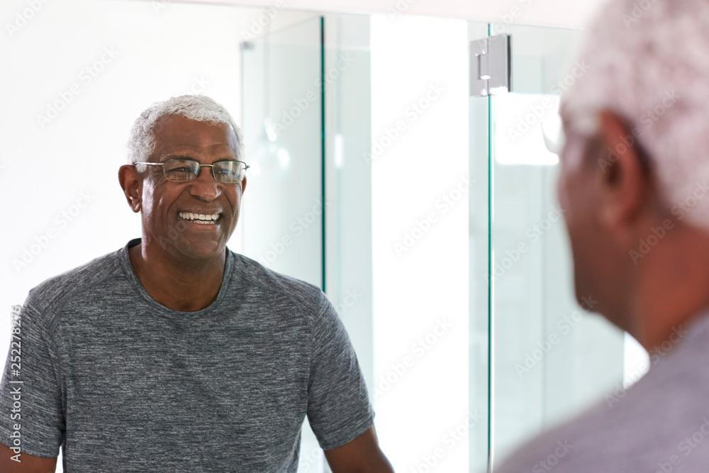 Fototapety, obrazy: Smiling Senior Man Looking At Reflection In Bathroom Mirror Wearing Pajamas