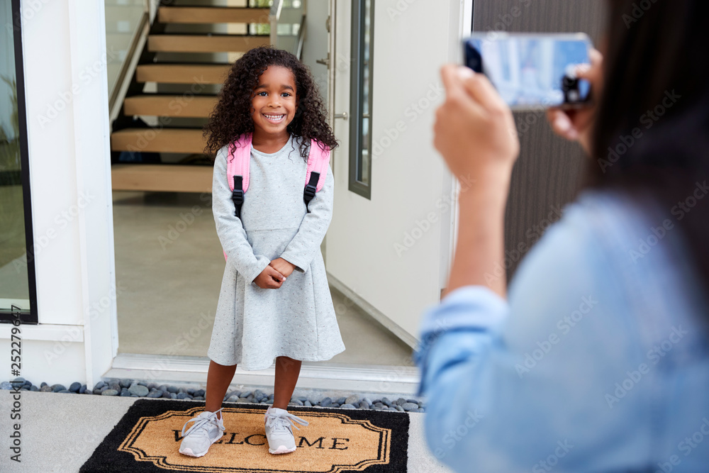 Fototapety, obrazy: Mother Taking Photo Of Daughter With Cell Phone On First Day Back At School