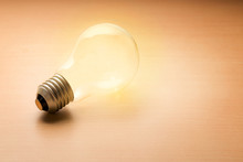 Empty Electric Light Bulb On Wooden Background, Start With A New Idea Concept