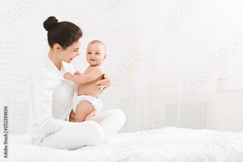 Obraz Young mother hugging her cute newborn child - fototapety do salonu