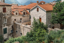 View Of The Old Town With Houses And Red-tiled Roofs And Wooden Shutters With A Mountain In The Background