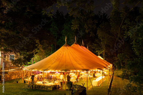 Obraz a wedding tent at night surrounded by trees with an orange glow from the lights, long exposure - wedding tent series - fototapety do salonu
