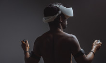 Rear View Of African Male Athlete With Naked Muscular Torso Using Oculus Rift Headset, Standing With Raised Hands Against Dark Background. Sport, Training , Workout And Virtual Reality Concept