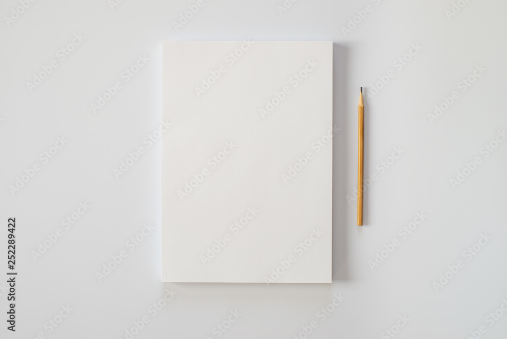 Fototapeta A stack of blank sheets of paper and a pencil on a white background