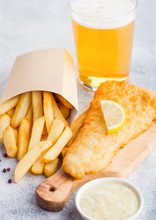 Traditional British Fish And Chips With Tartar Sauce Abd Glass Of Craft Lager Beer On Chopping Board On White Stone Table Background.