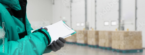 Fototapeta  Hand of worker with clipboard checking goods in freezing room or warehouse