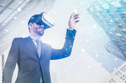 Valokuvatapetti Businessman in VR glasses, network interface city