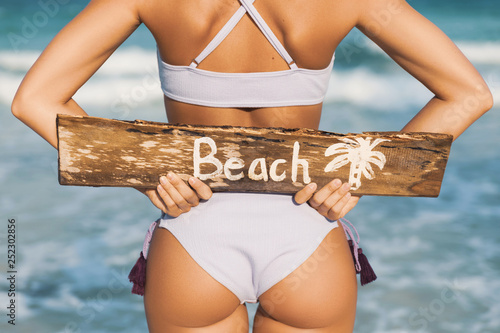 Fotografie, Obraz Sexy woman wearing swimsuit with old wooden sign on the beach