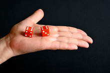 Red Game Cubes On The Male Palm, Gaming Dice Close Up, Selective Focus. Board Games.