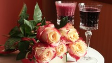 Red Sparkling Wine Is Poured Into Two Crystal Wineglass Against The Background Of A Bouquet Of Roses Lying On A White Table