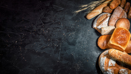 Asortiman svježe pečenog kruha na tamnoj podlozi. Bijeli i raženi kruh, lepinje s mjestom za kopiranje