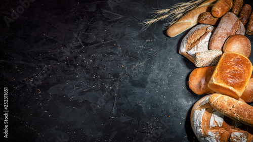 Poster Boulangerie Assortment of fresh baked bread on dark background. White and rye bread, buns with copy place