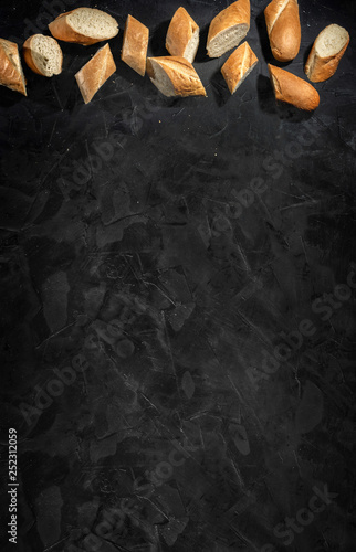 Poster Concrete Wallpaper Sliced fresh crunchy baguette on dark background. Top view with copy place