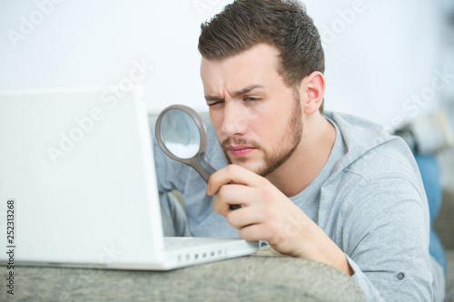man concentrated looking through a magnifying glass on his laptop Fototapeta