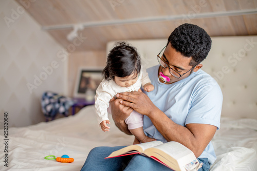 Photo attractive man in glasses is holding a baby girl and reading a book in the room